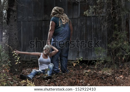 Horror scene of a woman being dragged by the hair by a hooded man by a cabin in the woods  - stock photo