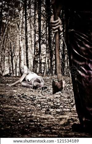 Horror scene of a woman crawling in the woods away from a man with an Axe.