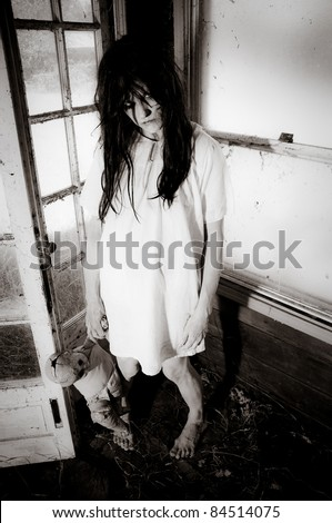Horror Scene of a Woman Possessed holding a doll standing in a corner - stock photo