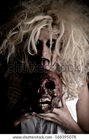 Horror Scene of a Woman Possessed licking a skull - stock photo