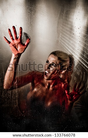 Horror Scene of a Woman with Bloody Hand against Wet Shower Glass - stock photo