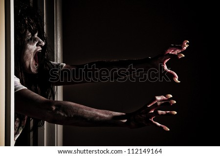 Horror Scene of a Zombie or Woman Possessed Grabbing out of Doorway - stock photo