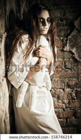 Horror scene: the scared crazy girl with moppet doll in hands - stock photo