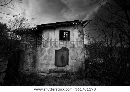 Horror scene with creepy old house and ghost shadow from the window, black and white high contrasted horor background   - stock photo