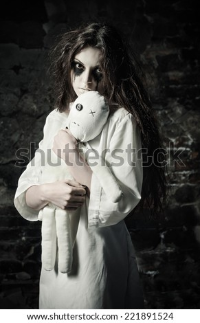 Horror shot: the sad strange girl with moppet doll in hands - stock photo
