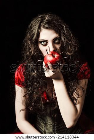 Horror shot: the strange scary girl eats apple studded with nails  - stock photo