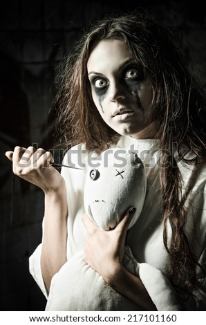 Horror style shot: a scary monster girl with moppet doll and needle in hands - stock photo