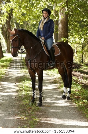 Horse and attractive female rider in the forest, rider smiling happy. - stock photo