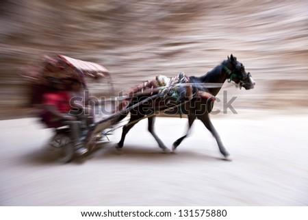 Horse and cart speeding through the Siq - stock photo