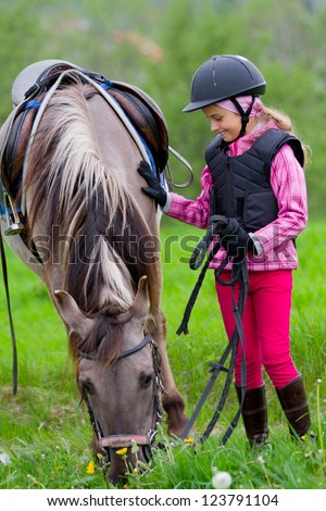 Horse and jockey - little girl is grazing the horse on the meadow - stock photo