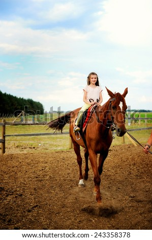 Horse and lovely brunette kid girl on the beauty summer day