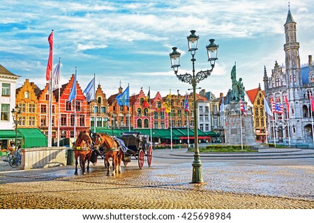 Horse carriages on Grote Markt square in medieval city Brugge at morning, Belgium. - stock photo