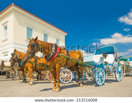 Horse drawn carts, used as taxis on the Greek island of Spetses, waiting for customers