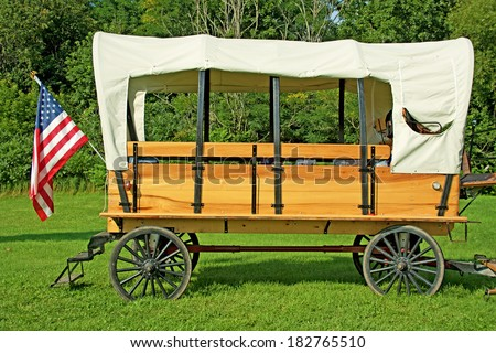 Horse drawn covered wagon with an American flag.