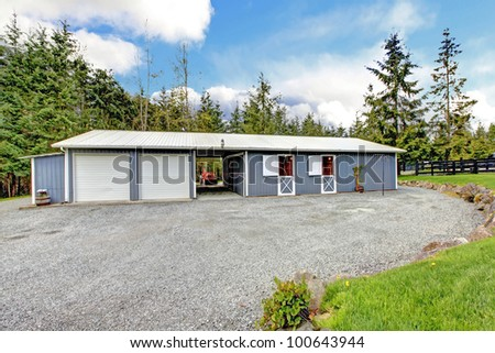 Horse farm building with stables and garage. - stock photo