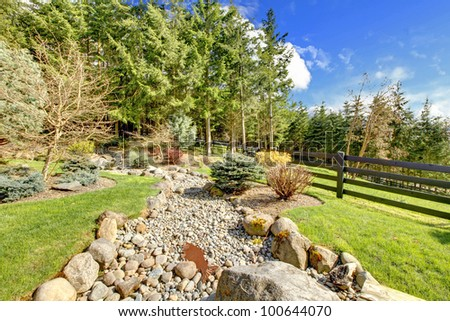 Horse farm rural landscape with rocks, forest and fence. - stock photo