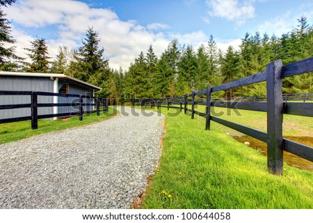 Horse farm with road, fence and shed with green grass. - stock photo