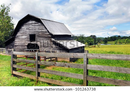 Horse grazes in the pasture close to a distant pond.  Barn and rustic wooden fence are both weathered and worn.  Blue sky and clouds make for perfect country scene. - stock photo