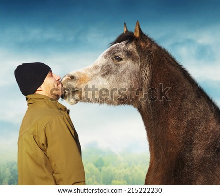 Horse kissing man in jacket and hat - stock photo