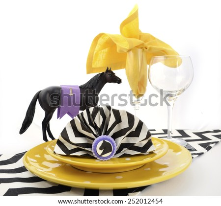 Horse racing carnival event luncheon table place setting in purple, yellow theme, and black and white chevron strip table runner. - stock photo