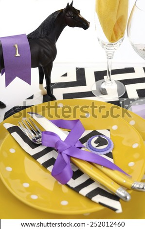 Horse racing carnival event luncheon table place setting in purple, yellow theme, and black and white chevron strip table runner, vertical. - stock photo