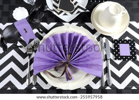 Horse racing carnival party luncheon table place setting in purple, black and white chevron stripe theme . - stock photo