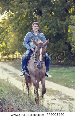horse ride young guy autumn forest - stock photo