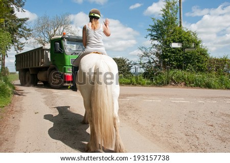 Horse rider waiting calmly for a truck to pass, while out for a hack - stock photo