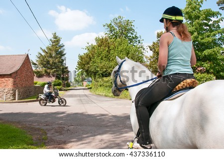 Horse rider waiting for a motorbike to go by