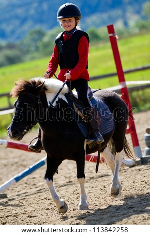 Horse riding - portrait of lovely equestrian on a horse - stock photo