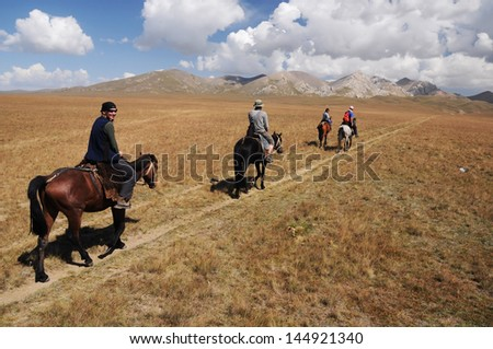 Horse riding trip in high mountain, Kyrgyzstan, Asia - stock photo