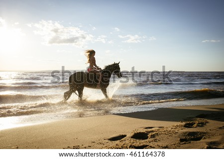 Horseback horse riding on coastline at the beach on sunset background