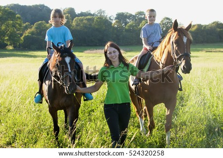 Horseback Riding Lessons - Woman Leading Two Horses with Boys