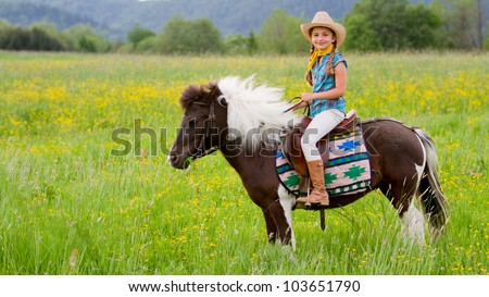 Horseback riding - lovely cowgirl is riding a pony - stock photo