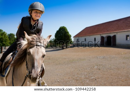 Horseback riding, lovely equestrian - little girl is riding a horse - stock photo