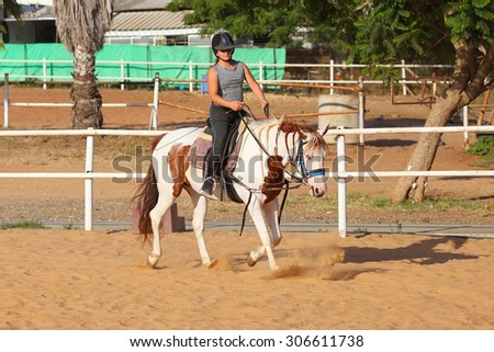 Horseback riding, lovely equestrian - young girl is riding a horse - stock photo