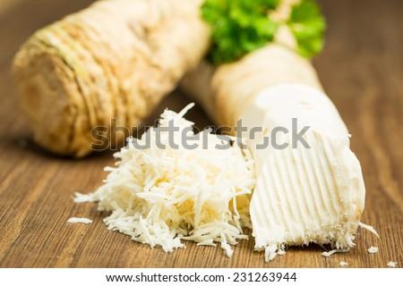 Horseradish on wooden board - stock photo