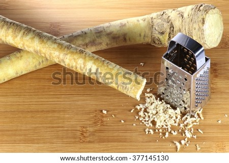 horseradish with grater on wooden background
