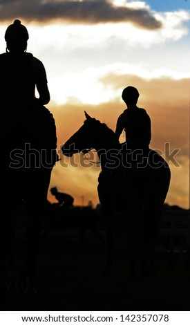 Horses doing morning track work during sunrise - stock photo