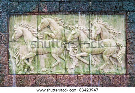 Horses in low relief statue cut out as jig saw image and water fall in front of.