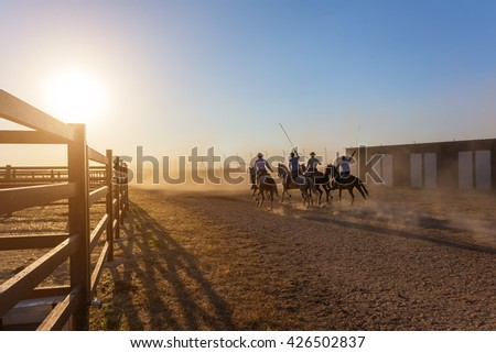 Horses running in corral at sunset. Riders escorted.