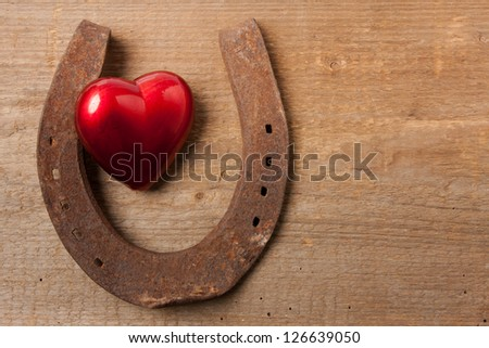 Horseshoe and a red heart on a wooden board