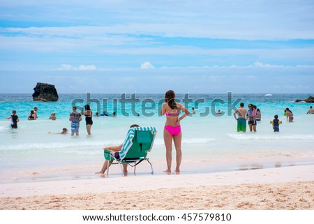 HORSESHOE BAY, BERMUDA - MAY 26 - An attractive lady in a pink bikini overlooks the pristine aqua marine colored water of Horseshoe Bay on May 26 2016 in Bermuda. - stock photo