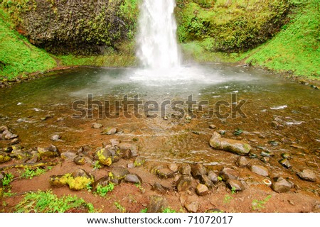 Horsetail Falls and pool of water filled with rocks - stock photo