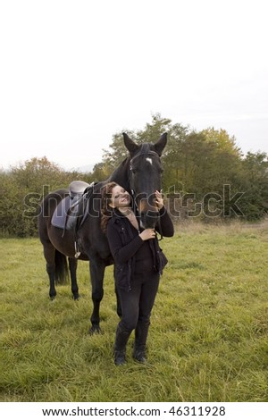 Horsewoman and horse stand in a meadow on a background of shrub.