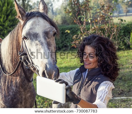 horsewoman takes a selfie with his horse to the country roads in autumn