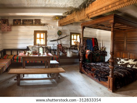 Hortitsa, Zaporozhye, 2015 JUNE. Zaporizhian Sich Cossack Museum. Inside antiquity abode bedchamber headman Ataman. Rich icon on shelf, luxury oak bed laid by fur rug, mahogany for eating. Indoor view - stock photo