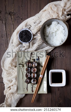 hosomaki sushi on plate with soy sauce, bowl of rice and sesame seeds on table - stock photo