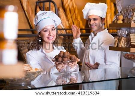Hospitable man and smiling girl offering pastry and chocolate sweets at bakery  - stock photo