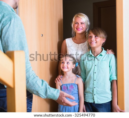 Hospitable man greeting cheerful  smiling guests at apartment entrance